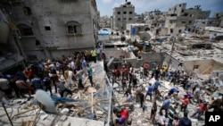 Палестинцы ищут выживших людей под обломками разрушенного авиаударами израильских ВВС дома в Газа Сити. 4 августа 2014 г.