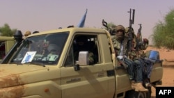 FILE - Members of an armed group sit in a vehicle in Kidal, Mali, July 13, 2016. Clashes have been reported in the restive northern city between pro-government and former rebel groups, both based there since February.