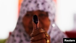 Seorang perempuan memperlihatkan jempol yang bertinta setelah memasukan suara di tempat pemungutan suara di Bogor, 9 Juli 2014. (Foto:dok)