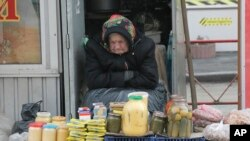 FILE - An elderly Ukrainian woman sells home made products in downtown Kyiv, Ukraine, Feb. 3, 2016.