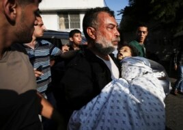 Akram Mogdadm holds the body of his son, Baraa, 6, who was killed along with 9 other people, all but one of them children, in an explosion at a park at Shati refugee camp, in the northern Gaza Strip, July 28, 2014.