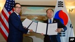 2019年10月17日,南韓財政部長洪楠基(右)和美國財政部長努欽在美韓加強基礎設施融資和市場建設合作框架簽署儀式上展示了雙邊協議。
