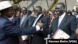 Rais Museveni mwenye kofia akimpa mkono hasimu wake wa kisiasa Besigye.