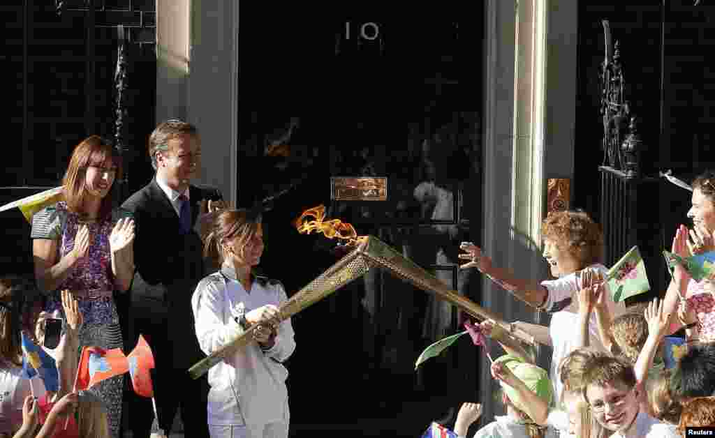 Britain's Prime Minister David Cameron (2nd L) and his wife Samantha (L) look on as Olympic torch bearer Florence Rowe (R) receives the flame from Kate Nesbitt (3rd L) in Downing Street, July 26, 2012.