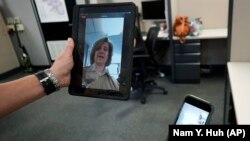 In this Friday, Aug. 13, 2021, photo Sheriff's Police Sgt. Bonnie Busching tests a video meeting from her personal electronic device with another person in the agency at the Cook County Sheriff's Office in Chicago. (AP Photo/Nam Y. Huh)