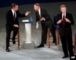 FILE - Then-President George H. W. Bush, talking with independent candidate Ross Perot as Democratic candidate Bill Clinton stands aside at the end of their second presidential debate in Richmond, Virginia, October 15, 1992.