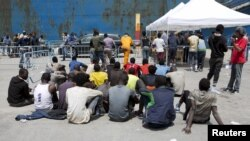 FILE - Migrants sit after disembarking from a merchant ship at the Sicilian harbor of Catania, southern Italy, May 5, 2015.