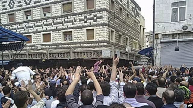 Mourners attend the funerals of protesters killed in earlier clashes in the Syrian city of Homs Apr18 2011