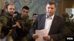 Pro-Russian rebel leader Alexander Zakharchenko prepares to casts his ballot during supreme council and presidential elections in the city of Donetsk, eastern Ukraine Sunday, Nov. 2, 2014.