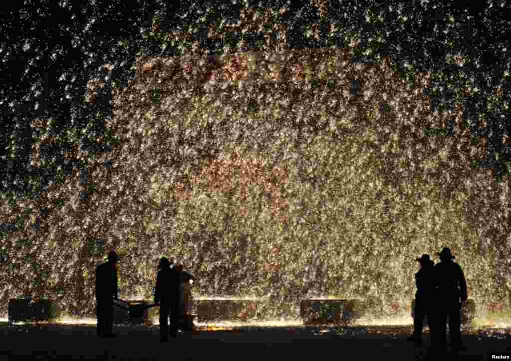 Performers spray molten iron against a concrete wall to celebrate the upcoming Lantern Festival in Nuanquan town of Yuxian County, Hebei province, China, March 1, 2015.