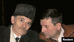 FILE - Crimean Tatar leader Mustafa Dzhemilev (L) speaks to a fellow Tatar in this 2006 photo.
