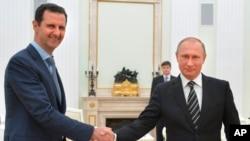 ប្រធានាធិបតីស៊ីរីលោក Bashar Al-Assad (ខាងឆ្វេង) ចាប់ដៃជាមួយប្រធានាធិបតីស៊ីរីលោក Vladmir Putin ។