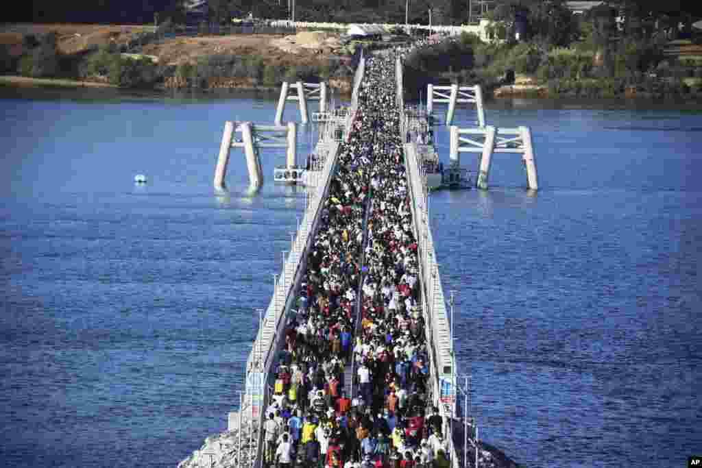 Hundreds of Mombasa residents cross the recently constructed floating foot bridge from Mombasa's Likoni mainland to the Mombasa Island, Kenya.