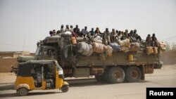FILE - Migrants sit on their belongings in the back of a truck as it is driven through a dusty road in the desert town of Agadez, Niger, headed for Libya, May 25, 2015.
