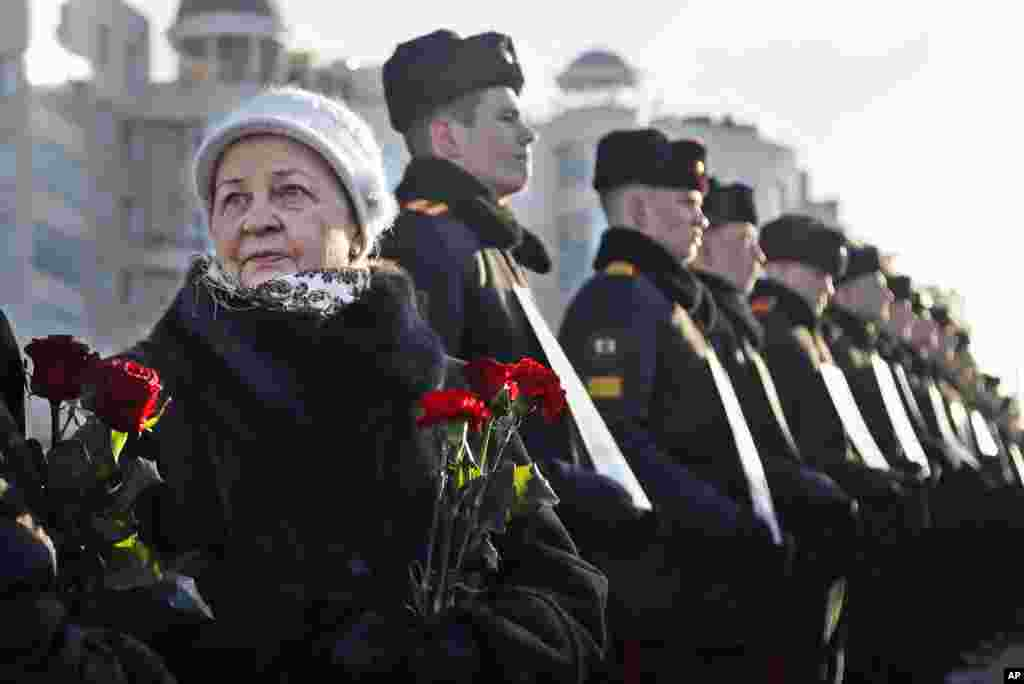 Women with flowers stand next to Belarusian military cadets holding portraits of soldiers who were killed during the Soviet war in Afghanistan, during a memorial ceremony on the Island of Tears in Minsk.