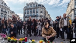 People light candles at a memorial set up outside the stock exchange in Brussels on March 22, 2016.