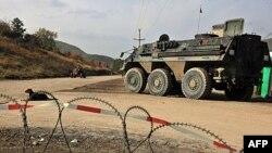 Binh sĩ NATO tuần tra gần rào cản của người Serb trong làng Zupce, 26/10/2011
