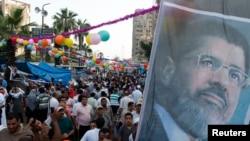 2013年8月8日埃及被推翻總統穆爾西的穆斯林兄弟會和穆爾西的支援群眾在慶祝標誌齋月結束的開齋節的第一天,在開羅舉行示威,高喊穆爾西的照片。