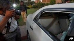 A Pakistani photographer takes photos of a bullet-riddled car belonging to journalist Hamid Mir parked at a local hospital in Karachi, Pakistan, April 19, 2014.