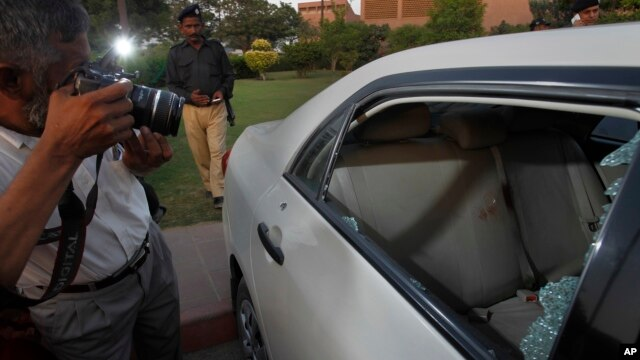 A Pakistani photographer takes photos of a bullet-riddled car belonging to journalist Hamid Mir parked at a local hospital in Karachi, Pakistan, April 19, 2014.