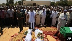 In this photo taken on a government-organized tour, Khaled, center, and Mohammed, center left, sons of Khoweildi al-Hamidi, a close associate of Moammar Gadhafi, left, pray among others next to bodies of two children during a funeral in the city of Surman