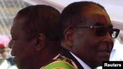 Zimbabwean President Robert Mugabe (R) and Prime Minister Morgan Tsvangirai arrive at a rally marking Zimbabwe's 31st independence anniversary celebrations in Harare, Zimbabwe, April 18, 2011.