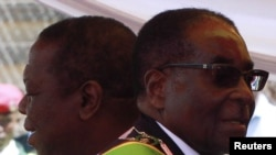 Zimbabwean President Robert Mugabe (R) and Prime Minister Morgan Tsvangirai arrive at a rally marking Zimbabwe's 31st independence anniversary celebrations in Harare, Zimbabwe, April 18, 2011.