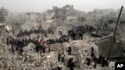 Cư dân đào bới tìm người sống sót dưới đống đổ nát của một tòa nhà bị phá hủy sau một vụ pháo kích của chính phủ Syria vào thành phố Aleppo.