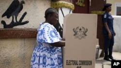 FILE - A woman fills in her ballots in presidential and parliamentary elections at a polling station in Accra, Ghana, Dec. 7, 2012. Women have made great strides in the political field in Ghana, though inequality still is considered by many to be widespread.