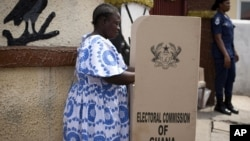 FILE - A woman fills in her ballots in presidential and parliamentary elections at a polling station in Accra, Ghana, Dec. 7, 2012.