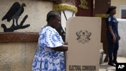 FILE - A woman fills in her ballots in presidential and parliamentary elections at a polling station in Accra, Ghana, Dec. 7, 2012. The electoral commission of Ghana has dismissed local media reports that the electoral body is not fully prepared to organize the anticipated November 7 presidential, parliamentary and local elections.