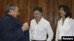 El presidente colombiano Juan Manuel Santos, centro, y su canciller María Angela Holguin, conversa con el presidente Raul Castro, en La Habana.