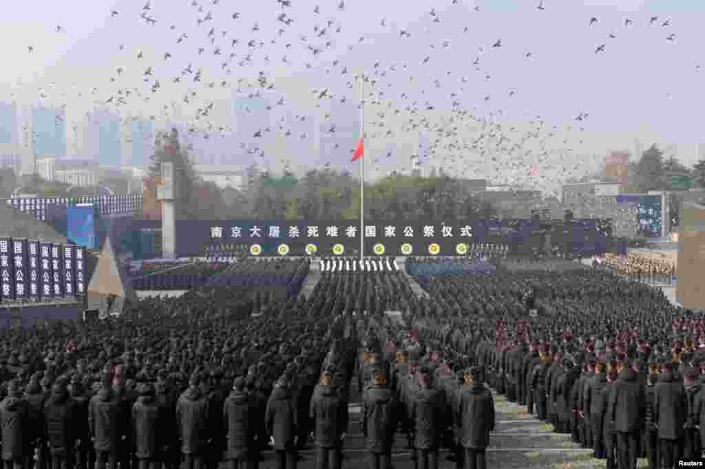 2018年12月13日,在中国江苏省南京举行南京大屠杀死难者国家公祭仪式 ,群众肃立,下半旗,和平鸽飞翔。