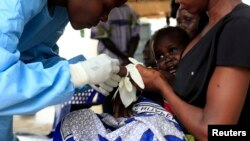 FILE - A South Sudanese baby suffering from cholera is being attended by medics in Juba Teaching Hospital, May 27, 2014.