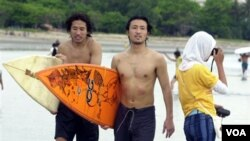 Dua turis Jepang berjalan di pinggiran pantai Kuta, Bali, usai berselancar. (Foto: dok)