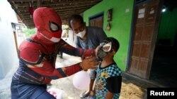 Agus Widanarko, 40, mengenakan kostum superhero saat menghibur anak laki-laki yang ibunya meninggal karena COVID-19, di Sukoharjo, Jawa Tengah, 10 September 2021. (Foto: Reuters)