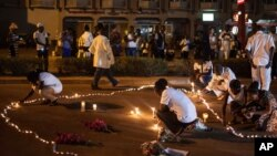 People light candles during a memorial ceremony for the victims of a recent hotel attack in which extremists killed at least 29 people in Ouagadougou, Burkina Faso, Jan. 23, 2016.