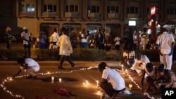 Des passants allument des bougies après l'attentat dans un hôtel à Ouagadougou, au Burkina Faso, le 23 janvier 2016.