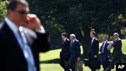 FILE - Members of President Donald Trump's administration walk past a Secret Service agent as they follow Trump to the Marine One helicopter on the South Lawn of the White House in Washington, Aug. 4, 2017. After Trump's controversial remarks on the violence in Charlottesville there is rising speculation that some top officials may be looking for way out.
