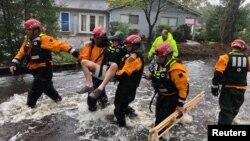 Tim penyelamat membantu evakuasi seorang warga di River Bend, North Carolina yang dilanda badai Florence, Jumat (14.9).