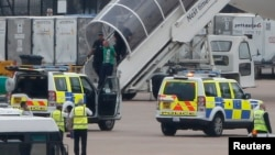 A man is escorted off a Qatar Airways aircraft by police at Manchester airport in Manchester, northern England, Aug. 5, 2014.