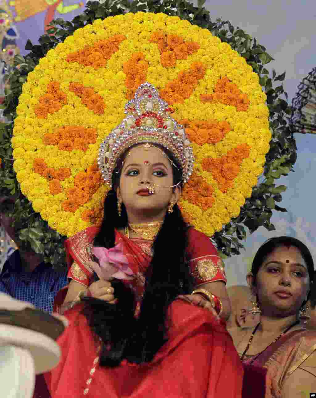 """A young girl sits for the """"Kumari Puja"""" ritual at the Ram Krishna mission temple in Dhaka, Bangladesh. Kumari Puja is part of Durga Puja festival where a young girl is worshipped symbolically as a goddess."""