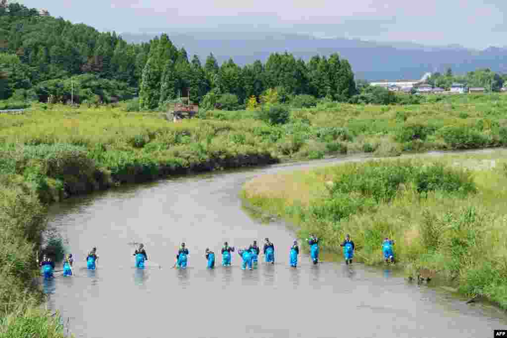 Police officers search for missing people in a river in Namie, near the striken TEPCO's Fukushima Dai-ichi nuclear plant in Fukushima prefecture, two and half years after the massive earthquake and tsunami, which killed more than 18,000 people in northern Japan.