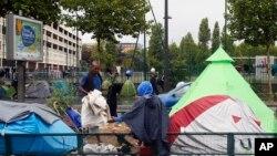 Migran duduk bersama di pemukiman migran darurat di kawasan La Chapelle di tepi utara kota Paris, Perancis, 17 Agustus 2017. (Foto: dok).