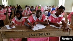 Shade Ajayi, 50, takes notes during class at Ilorin Grammar School in Ilorin, Kwara state, March 25, 2021. R