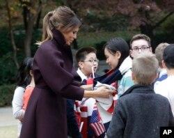 7일 청와대를 방문한 도널드 트럼프 미국 대통령의 부인 멜라니아 여사가 어린이 환영단의 한 소녀에게 목도리를 걸어주고 있다.