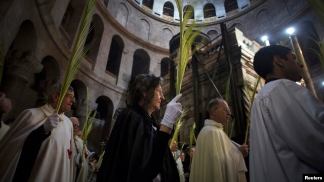 Christian clergy and worshipers hold palm fronds during a procession in the Church of the Holy Sepulcher in Jerusalem's Old City March 24, 2013.