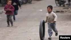一个叙利亚小男孩在街上推着轮胎奔跑