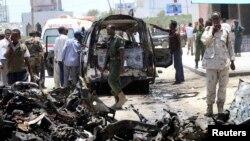 Một binh sĩ dùng điện thoại di động để thu hình tại hiện trường sau vụ nổ bom trong thủ đô Mogadishu của Somalia, 18/3/13