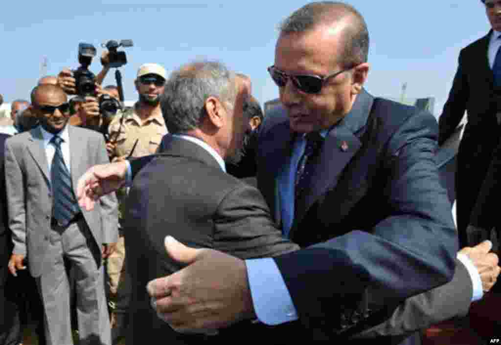 Libyan Transitional National Council chairman Mustafa Abdel Jalil, left, and Turkish Prime Minister Recep Tayyip Erdogan embrace each other upon Erdogan's arrival at Tripoli Airport, Libya, Friday, Sept. 16, 2011. Erdogan, intent on broadening Turkey's i
